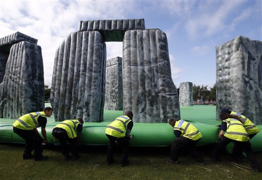 "Workers install ""Sacrilege"", a life-sized inflatable replica of Stonehenge, Saturday, July 21, 2012, in Greenwich Peninsula, London. Opening ceremonies for the 2012 London Olympics will be held Friday, July 27. (AP Photo/Jae C. Hong)"