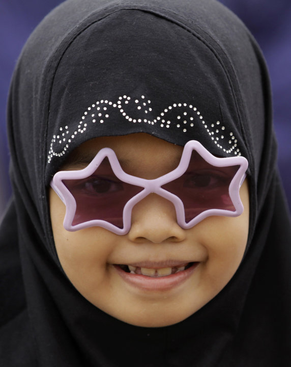 A Filipino Muslim girl wearing sunglasses smiles as they celebrate Eid-al Fitr at Manila's Rizal Park, Philippines on Sunday Aug. 19, 2012. Eid al-Fitr marks the end of the holy month of Ramadan. (AP