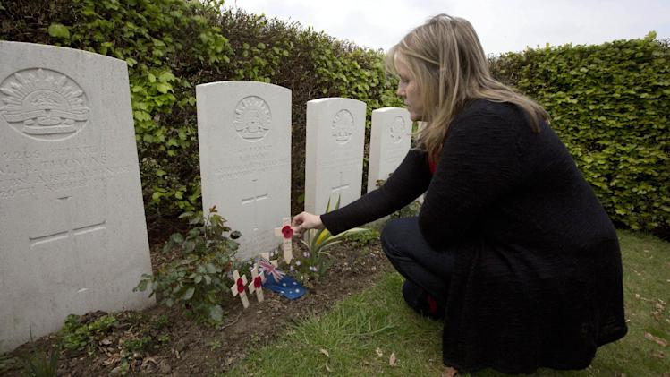 In this Thursday, April 24, 2014 photo, Kaylene Biggs, great-granddaughter of World War I Australian soldier Andrew Bayne, places a wooden cross with a poppy and a message on the grave at Westhof Farm Commonwealth Cemetery in Nieuwkerke, Belgium on Thursday, April 24, 2014. Bayne's grave lies among the 131 Commonwealth soldiers and a handful of German soldiers in this small cemetery surrounded by a landscape still scarred by countless bomb craters, rusting gas shells, bunkers and trenches. (AP Photo/Virginia Mayo)