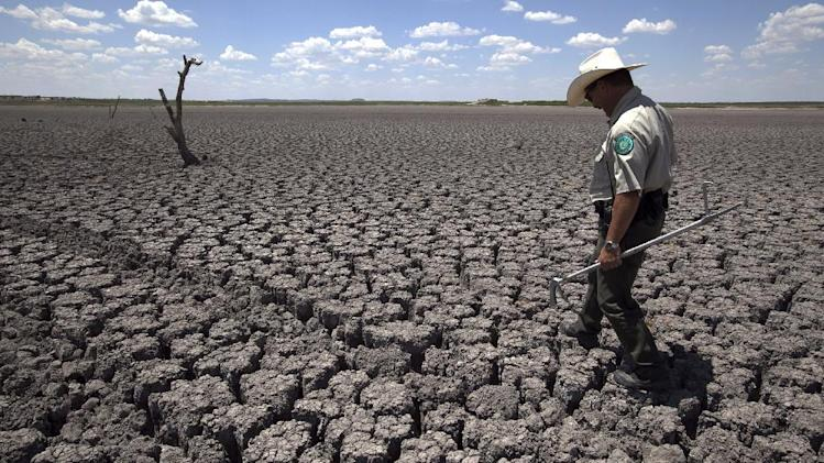 In this Wednesday, Aug. 3, 2011 file photo, Texas State Park police officer Thomas Bigham walks across the cracked lake bed of O.C. Fisher Lake in San Angelo, Texas. A combination of the long periods of 100-plus degree days and the lack of rain in the drought-stricken region has dried up the lake that once spanned over 5400 acres. The year 2011 brought a record heat wave to Texas, massive floods in Bangkok and an unusually warm November in England. How much has global warming boosted the chances of events like that? Quite a lot in Texas and England, but apparently not at all in Bangkok, according to new analyses released Tuesday, July 10, 2012. Researchers calculated that global warming has made such a Texas heat wave about 20 times more likely to happen during a La Nina year. (AP Photo/Tony Gutierrez)