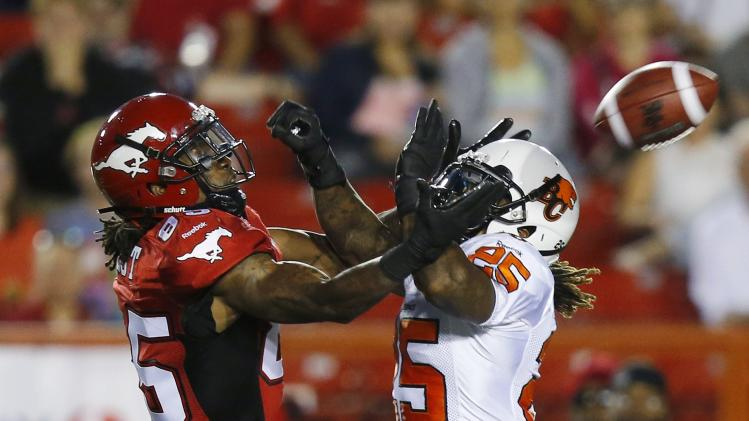 Calgary Stampeders' West is blocked from catching a pass by BC Lions' Yell during their CFL football game in Calgary