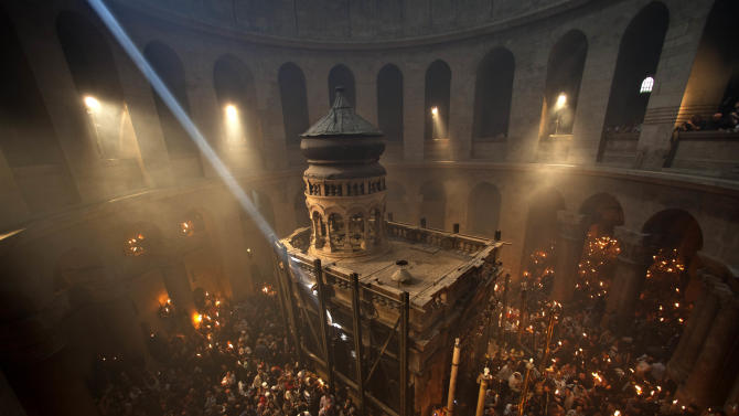 Christian pilgrims hold candles at the Church of the Holy Sepulchre, traditionally believed to be the burial site of Jesus Christ, during the ceremony of the Holy Fire in Jerusalem's Old City, Saturday, April 14, 2012. (AP Photo/Sebastian Scheiner)
