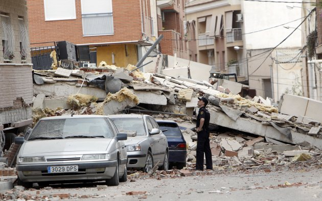 FILE - In this May 12, 2011 file photo, a police officer inspects damage caused by an earthquake the previous day in Lorca, Spain, Thursday, May 12, 2011. Farmers drilling ever deeper wells over decades to water their crops likely contributed to a deadly earthquake in southern Spain last year, a new study suggests. The findings may add to concerns about the effects of new energy extraction and waste disposal technologies. (AP Photo/Alberto Saiz, File)