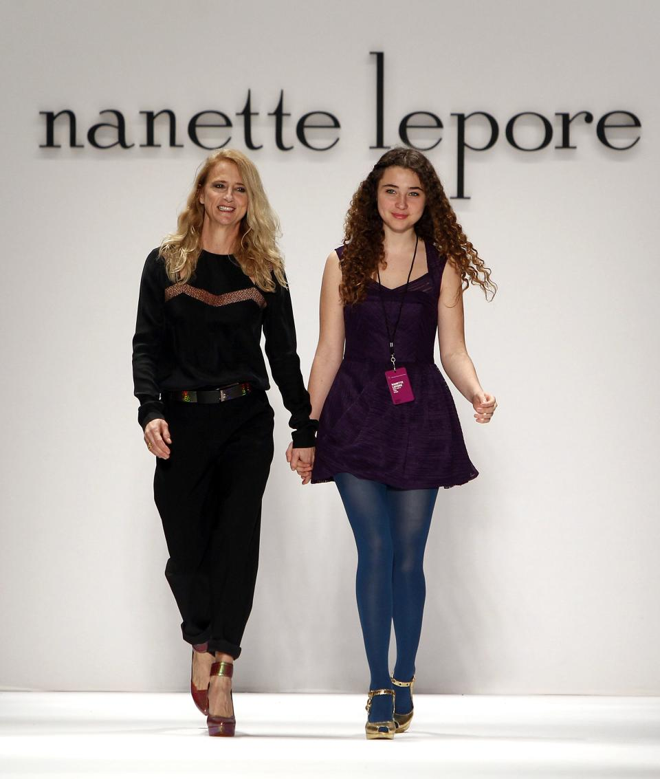 Designer Nanette Lepore, left, is joined by her daughter Violet as she acknowledges the audience after the Nanette Lepore Fall 2013 collection show during Fashion Week, Wednesday, Feb. 13, 2013 in New York. (AP Photo/Jason DeCrow)