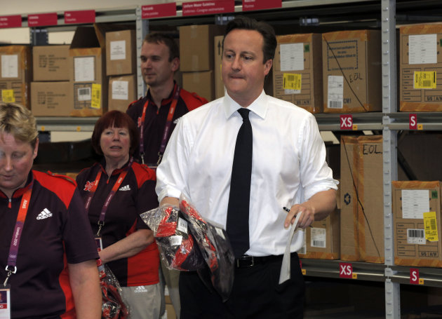 British Prime Minister David Cameron works with London 2012 Olympic and Paralympic Games volunteers during a visit to coincide with one month to go to the 2012 Games at the Uniform Distribution and Accreditation Centre, (UDAC) in east London, Tuesday, June 26, 2012. (AP Photo/Lefteris Pitarakis, pool)