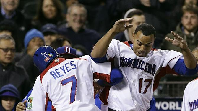 The Dominican Republic's Jose Reyes (7) celebrates with Nelson Cruz (17) after scoring against the Netherlands during the fifth inning of a semifinal game of the World Baseball Classic in San Francisco, Monday, March 18, 2013. (AP Photo/Eric Risberg)
