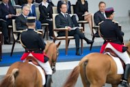 Francois Hollande (centre) started the day by reviewing the traditional Bastille Day military parade in Paris that saw soldiers, sailors and gendarmes march down the Champs Elysee avenue from the Arc de Triomphe, with fighter jets and other military planes flying overhead