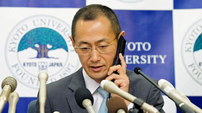 Kyoto University Professor Shinya Yamanaka receives a call from Japanese Prime Minister Toshihiko Noda to congratulate his winning of Nobel Prize during a news conference at Kyoto University in Kyoto, Japan, Monday night, Oct. 8, 2012. Yamanaka and British researcher John Gurdon won this year's Nobel Prize in physiology or medicine. (AP Photo/Kyodo News) JAPAN OUT, MANDATORY CREDIT, NO LICENSING IN CHINA, FRANCE, HONG KONG, JAPAN AND SOUTH KOREA