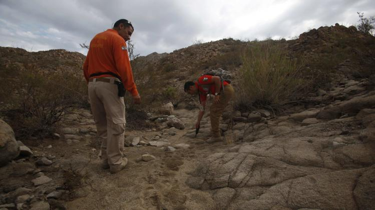 Grupo Beta members look at footprints while searching in the mountains between Mexico and the U.S. for potential border crossers during a patrol on the outskirts of Ciudad Juarez