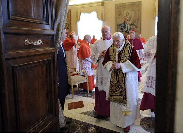 In this photo provided by the Vatican newspaper L'Osservatore Romano, Pope Benedict XVI, center, leaves after attending a meeting of Vatican cardinals where he read a document in Latin in which he ann