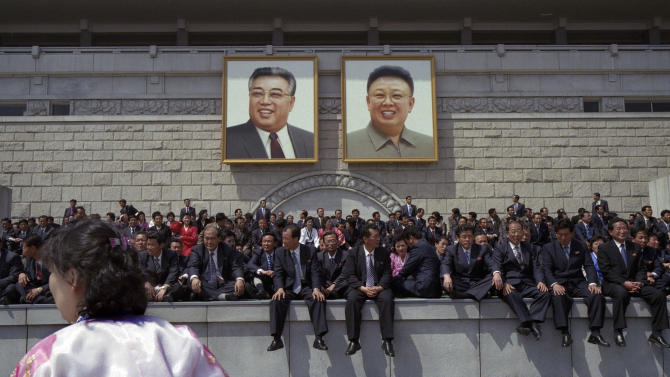 In this April 15, 2012 photo, North Koreans rest under portraits of the late leaders, Kim Il Sung, left, and Kim Jong Il, at the end of a mass military parade in Pyongyang's Kim Il Sung Square to celebrate 100 years since the birth of Kim Il Sung. (AP Photo/David Guttenfelder)