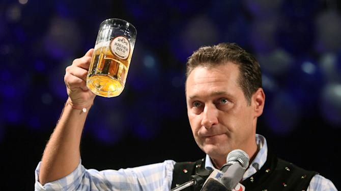 FILE - In this Feb. 22, 2012 file photo head of the Austrian right-wing Freedom Party Heinz-Christian Strache lifts a glass of beer during his traditional Ash Wednesday speech in Ried, Austria. The head of Vienna's Jewish community is criticizing Austria's rightist leader for posting a cartoon showing a banker with a large hooked nose and Star of David cufflinks profiting from Europe's financial crisis. Austrian authorities are investigating who posted the cartoon on Strache's Facebook page and may charge the perpetrator with a criminal offense, an official said Tuesday, Aug. 21, 2012. (AP Photo/dapd, Rudolf Brandstaetter)