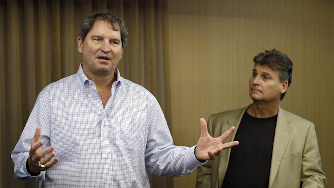 """In this Jan. 10, 2013 file photo, former Cleveland Browns quarterback Bernie Kosar, left, speaks at a news conference with Dr. Rick Sponaugle, in Middleburg Heights, Ohio . Thursday, Jan. 10, 2013. Kosar believes he's been unfairly sacked as a TV broadcaster. Kosar contends he's been removed because of slurred speech he attributes to """"a direct result of the many concussions I received while playing in the NFL."""""""