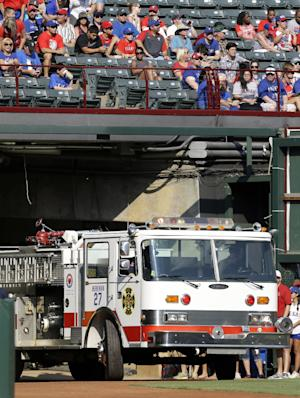 Fans watch as a fire truck donated to the West, Texas, fire department by Texas Rangers' Lance Berkman with assistance from the Arlington, Texas, Fire Department, is pulled out of the left field tunnel before the Rangers' baseball game against the Houston Astros on Saturday, July 6, 2013, in Arlington, Texas. (AP Photo/Tony Gutierrez)