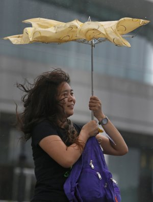 A tourist from mainland China braves strong wind near…