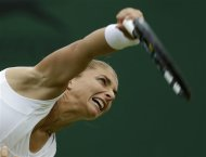 Sara Errani of Italy serves to Coco Vandeweghe of the United States during a first round women's singles match at the All England Lawn Tennis Championships at Wimbledon, England, Tuesday, June 26, 2012. (AP Photo/Alastair Grant)