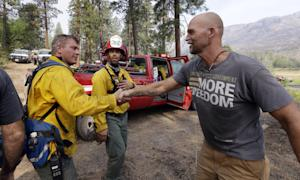 Homeowner Brad Craig, right, thanks departing firefighters…