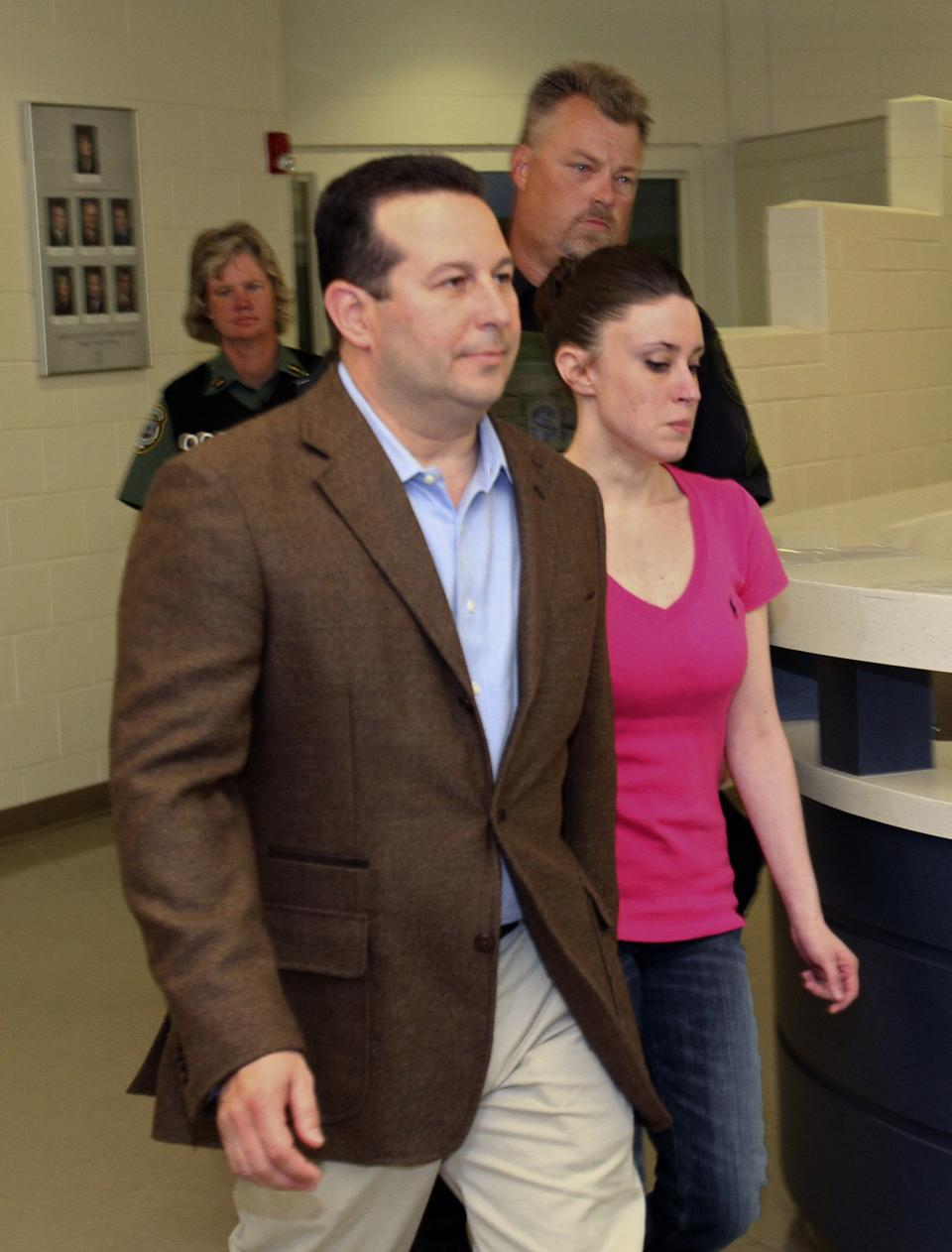 Casey Anthony, front, walks out of the   the Orange County Jail with her attorney Jose Baez, left,  during her release in Orlando, Fla., early Sunday, July 17, 2011.  Anthony was acquitted last week of murder in the death of her daughter, Caylee. (AP Photo/Red Huber, Pool)