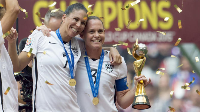 FILE- In this July 5, 2015, file photo, United States' Shannon Boxx, left, and Christie Rampone celebrate their win after they defeated Japan 5-2 in the FIFA Women's World Cup soccer championship in Vancouver, British Columbia, Canada. U.S. soccer formally announced Monday, July 27, 2015, that midfielders Lauren Holiday and Boxx will retire from the U.S. national team following a victory tour to celebrate the Women's World Cup title. (Jonathan Hayward/The Canadian Press via AP, File) MANDATORY CREDIT