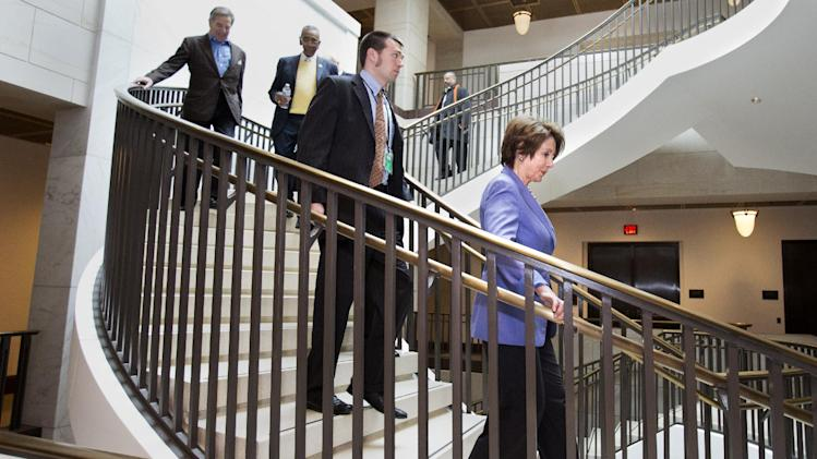 House Minority Leader Nancy Pelosi of Calif., right, walks down a staircase on Capitol Hill in Washington, Tuesday, Jan. 1, 2013, to a Democratic caucus meeting with Vice President Joe Biden. Squarely in the spotlight, House Republicans began deciding their next move Tuesday after the Senate overwhelmingly approved compromise legislation negating a fiscal cliff of across-the-board tax increases and sweeping spending cuts to the Pentagon and other government agencies.  (AP Photo/Jacquelyn Martin)