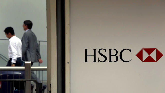 FILE - In this July 30, 2012, file photo, ,People walk past a logo of HSBC headquarters in Hong Kong.  HSBC, Europe's biggest bank, has set aside an additional  $1.15 billion to cover potential U.S. fines for money laundering by its Mexican unit and penalties for mis-selling payment protection insurance. (AP Photo/Vincent Yu, File)