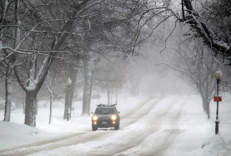 A lone vehicle travels along the Ashland Avenue Tuesday morning Feb. 26, 2013 in St. Joseph, Mo., as the snow storm continues to hit the area. This is the second winter storm that has hit the Midwest in a week. (AP Photo/St. Joseph News-Press, Jessica Stewart)
