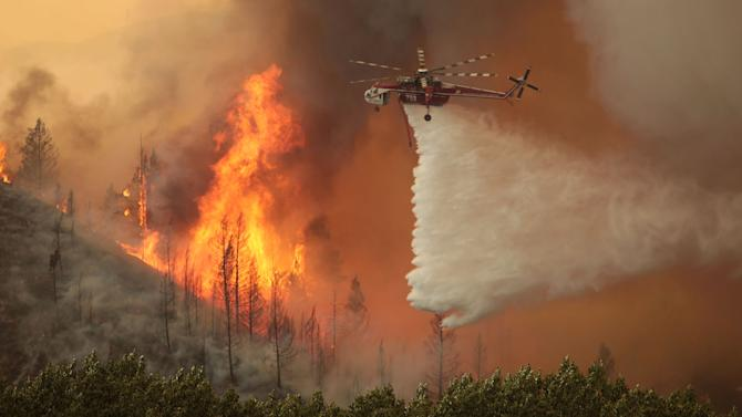 Helicopters battle the 64,000 acre Beaver Creek Fire on Friday, Aug., 16, 2013 north of Hailey, Idaho. A number of residential neighborhoods have been evacuated because of the blaze.(AP Photo/Times-News, Ashley Smith) MANDATORY CREDIT