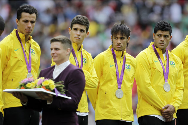 Brazil players react on the podium as they receive the silver medal during a ceremony following their loss to Mexico in the men's soccer final at the 2012 Summer Olympics, Saturday, Aug. 11, 2012, in
