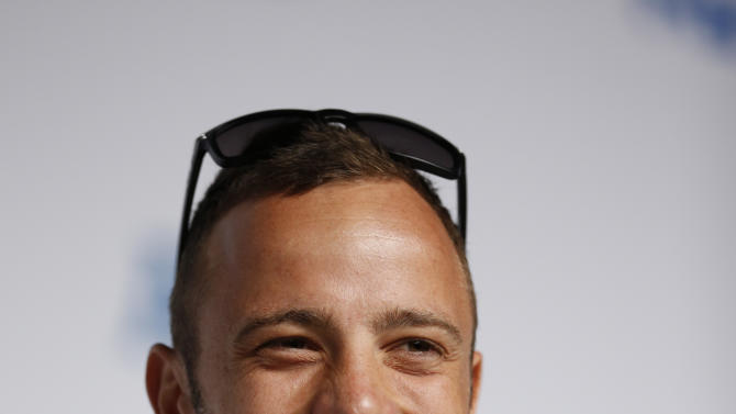 South African Paralympic runner Oscar Pistorius smiles as he speaks during a news conference at the 2012 Paralympics, Tuesday, Aug. 28, 2012, in London.  Pistorius became the first double leg amputee to participate in the Olympics at the London 2012 Summer Olympics.  (AP Photo/Matt Dunham)