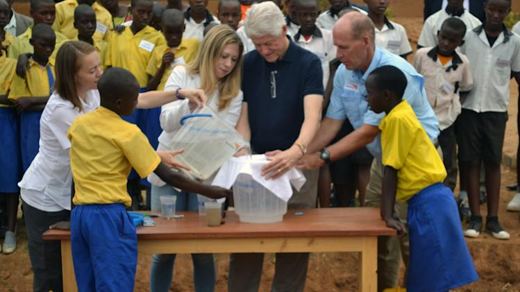President Clinton and daughter Chelsea, middle, gesture after purifying a bucket of dirty water to safe drinking water Monday Aug. 5, 2013 at Group Scolaire Camp Kanombe outside the capital Kigali. President Clinton was on a two-day visit to the central African country as part of his African tour which took him to Malawi and South Africa. Looking on is Dr Greg Alllgood of World Vision, second right, and Allison Tummon Kamphuis , second left,from Proctor & Gamble as well as school children from rural Rwanda. President Clinton also launched a malnutrition drive together with the government of Rwanda and World Food Programme before departing for South Africa. (AP Photo)