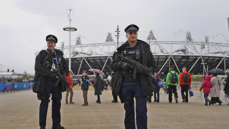 FILE  This , Saturday, May 5, 2012 file photo shows armed British police officers posing for photographers whilst patrolling during the British Universities and Colleges Sport Athletics Championship (BUCS) outside the Olympic Stadium in the Olympic Park in London. Britain is pouring more money into plans to control the massive crowds expected in London during the Olympics, with the government acknowledging Wednesday June 13, 2012 that it had vastly underestimated the number of people likely to take part in the heady atmosphere of the city.     (AP Photo/Matt Dunham)