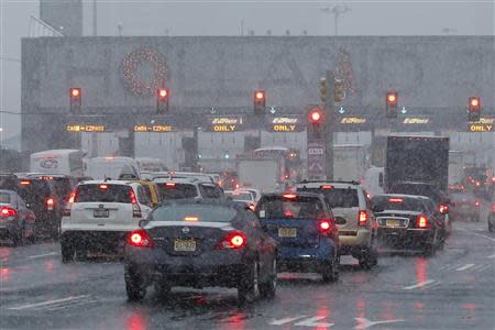 Vehicles wait in line to go through the Holland tunnel to New York City during the arrival of a snowstorm in Newport