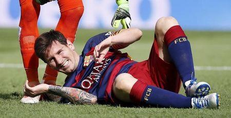 Barcelona's Lionel Messi grimaces as he lies on the pitch after injuring his left knee during their Spanish first division soccer match against Las Palmas at Camp Nou stadium in Barcelona