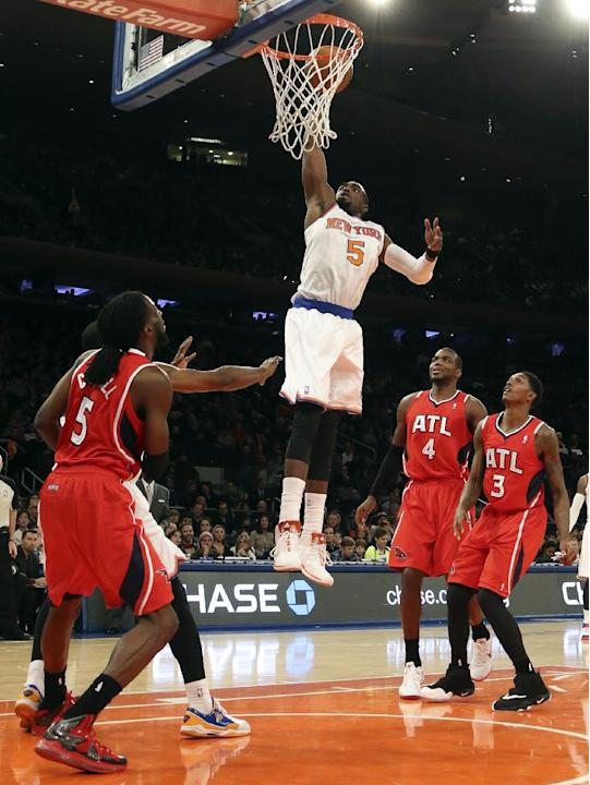 New York Knicks shooting guard Tim Hardaway Jr. (5) dunks as Atlanta Hawks forward DeMarre Carroll (5), forward Paul Millsap (4), and shooting guard Louis Williams (3) stand near during the first half