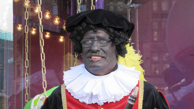 """In this photo taken Sunday, Nov. 18, 2012 a musician dressed as """"Zwarte Piet"""" or """"Black Pete"""" pauses during a parade after St. Nicholas, or Sinterklaas, arrived by boat in Amsterdam, Netherlands, Sunday, Nov. 18, 2012. Foreigners visiting the Netherlands in winter are often surprised to see that the Dutch version of St. Nicholas' little helpers resemble a racist caricature of a black person. The overwhelming majority of Dutch, who pride themselves on tolerance, are fiercely devoted to their holiday tradition and say """"Zwarte Piet"""", whose name means """"Black Pete"""", is absolutely harmless, a fictional figure who does not represent any race. But now a growing group of Dutch natives are questioning whether this particular part of the tradition should be changed. (AP Photo/ Margriet Faber)"""