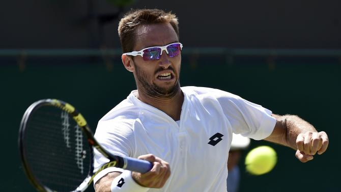 Viktor Troicki of Serbia hits a shot during his match against Dustin Brown of Germany at the Wimbledon Tennis Championships in London