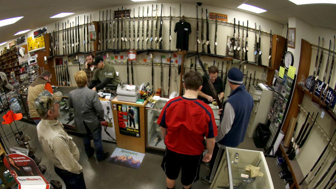 FILE - In this Jan. 16, 2013 file photo, taken with a fisheye lens, customers line up at the gun counter at Duke's Sport Shop in New Castle, Pa. The FBI posted new data for gun background checks covering through January 2013 that says gun checks *dropped* more than 10 percent nationwide, from roughly 2.8 million in December 2012 to 2.5 million in January 2013.  (AP Photo/Keith Srakocic, File)