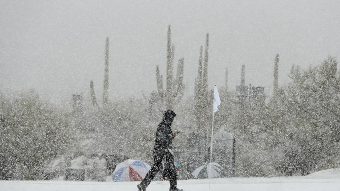 CORRECTS THE DAY AND DATE - A volunteer walks along the practice green as snow falls during the Match Play Championship golf tournament, Wednesday, Feb. 20, 2013, in Marana, Ariz. Play was suspended. (AP Photo/Ross Franklin)