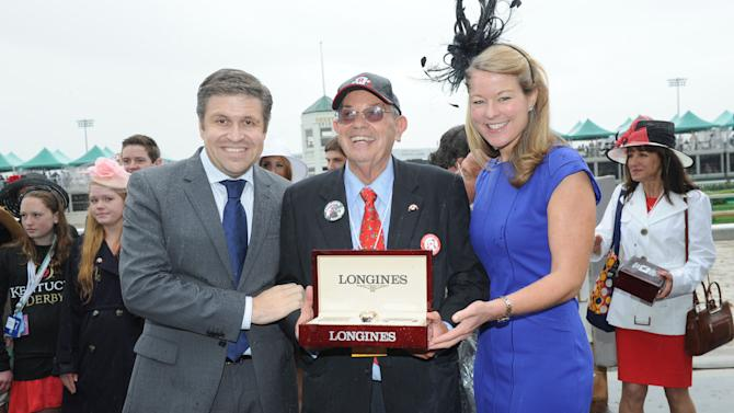 IMAGE DISTRIBUTED FOR LONGINES - Jennifer Judkins, right, and Juan-Carlos Capelli, left, both of Longines, award owner Kenneth L. Ramsey with his Longines timepiece after his horse Stephanie's Kitten won the Churchill Distaff Turf Mile presented by Longines, Saturday, May 4, 2013, in Louisville, Ky.,  Longines, the Swiss watchmaker known for its famous timepieces, is the Official Watch and Timekeeper of the 139th annual Kentucky Derby. (Photo by Diane Bondareff/Invision for Longines/AP Images)
