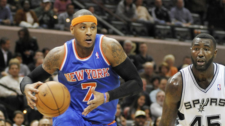 New York Knicks' Carmelo Anthony, left, drives around San Antonio Spurs' DeJuan Blair during the first half of an NBA basketball game on Thursday, Nov. 15, 2012, in San Antonio. (AP Photo/Darren Abate)