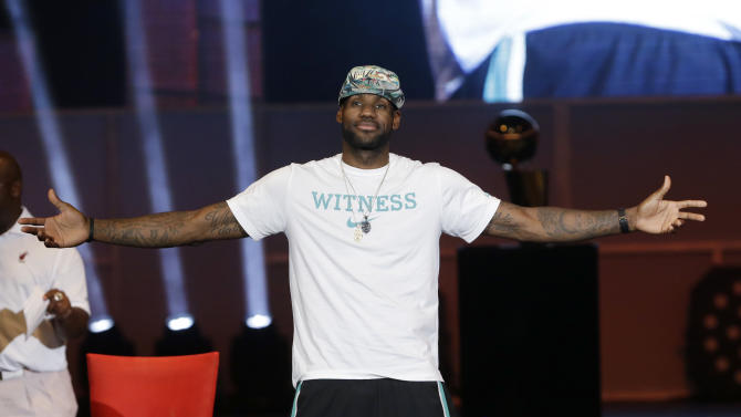 Miami Heat forward LeBron James reacts as he is introduced, Monday, June 24, 2013, during a celebration for season ticket holders at the American Airlines Arena in Miami. The Heat defeated the San Antonio Spurs 95-88 in Game 7 to win their second straight NBA championship. (AP Photo/Wilfredo Lee)