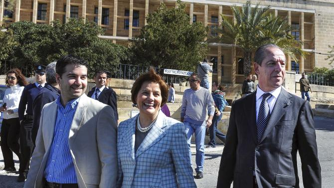 Maltese Prime Minister Lawrence Gonzi, right, arrives to casts his ballot with his wife Catherine Callus and their son Paul, in Valletta, Malta, Saturday, March 9, 2013. Maltese head to the polls Saturday to decide whether to grant the center-right Nationalist Party a fourth straight term or give the opposition a shot at government after 15 years. (AP Photo/Lino Arrigo Azzopardi)