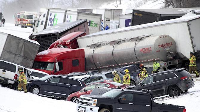 Emergency personnel work at the scene of a fatal crash near Fredericksburg, Pa., Saturday, Feb. 13, 2016. The pileup left tractor-trailers, box trucks and cars tangled together across several lanes of traffic and into the snow-covered median. (Daniel Zampogna/PennLive.com via AP) MANDATORY CREDIT; MAGS OUT