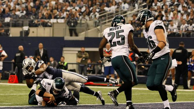 Philadelphia Eagles quarterback Mark Sanchez (3) scores a touchdown as he is tackled by Dallas Cowboys free safety J.J. Wilcox (27) during the first half of an NFL football game Thursday, Nov. 27, 2014, in Arlington, Texas