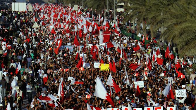 "In This March 4, 2011, file photo Tens of thousands of Bahraini anti-government protesters march from the main government house in the capital of Manama, Bahrain, to the Pearl roundabout, where they have set up camp. The sign reading ""Down Khalifa"" refers to Prime Minister Khalifa Al Khalifa. (AP Photo/Hasan Jamali)"