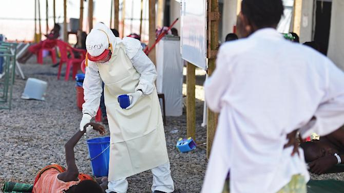 A health worker wearing protective equipment assists an Ebola patient at the Kenama treatment centre run by the Red Cross Society on November 15, 2014 in Sierra Leone
