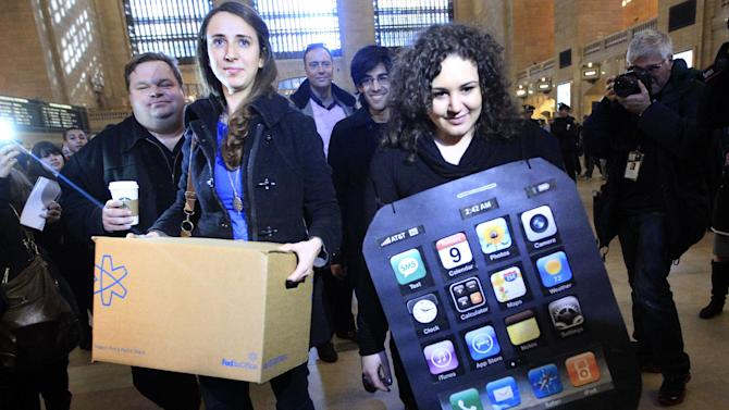 FILE - In this Feb. 9, 2012 file photo, Sarah Ryan, left, and Shelby Knox, with Change.org arrive at the Apple store at Grand Central to deliver petitions asking Apple to change its manufacturing practices and to address criticism of worker conditions at manufacturing partners operating in China, in New York. Apple said Monday, Feb. 13, 2012, that an independent group, the Fair Labor Association, has started inspecting the working conditions in the Chinese factories where its iPads and iPhones are assembled. (AP Photo/Mary Altaffer, File)