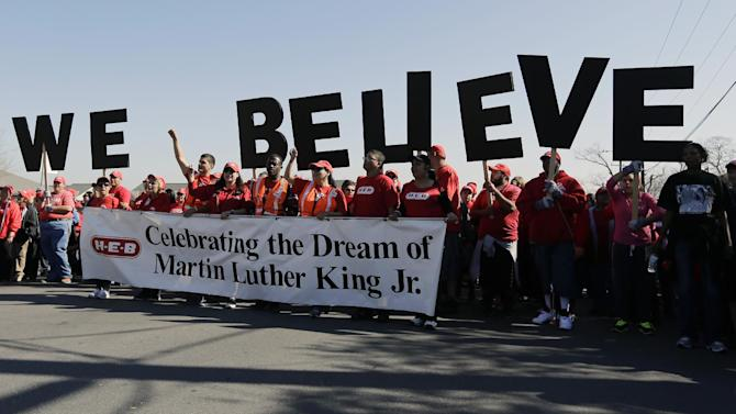 """Letters spelling """"We Believe"""" are carried by a group during a march honoring Martin Luther King Jr., Monday, Jan. 20, 2014, in San Antonio. (AP Photo/Eric Gay)"""