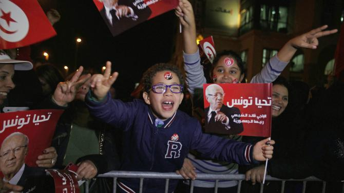 Nidaa Tounes supporters wave flags and shout slogans as they celebrate after Essebsi won the country's first free presidential election, in Tunis