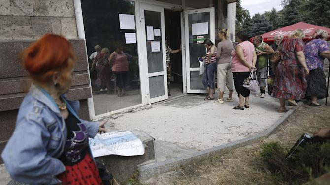 Local residents stand in line to get benefit payments outside the rebel headquarters in Donetsk, eastern Ukraine, Tuesday, Aug. 19, 2014. A crowd formed outside the rebel headquarters, once the Donetsk region administrative building, in Donetsk amid rumors that pension and disability payments and child assistance were being given out. (AP Photo/Max Vetrov)